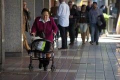 Escena urbana: Una señora inválida que camina en Sevilla Foto de archivo libre de regalías
