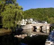 Esch sur Sure in Luxembourg. Medieval Village Esch sur Sure with Classical Houses and Bridge over Reflection in Sunny Day on Blue Sky background Outdoors Stock Photos