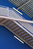 Escher stairs over blue wall. Outside stairs of a blue building stock photo