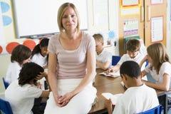 ESchoolchildren e sua leitura do tacher na classe Imagem de Stock