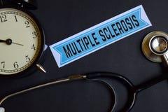 Esclerosis múltiple en el papel de la impresión con la inspiración del concepto de la atención sanitaria despertador, estetoscopi foto de archivo