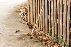 Escoba contra la cerca de madera, cerca casera, textura del fondo Foto de archivo libre de regalías