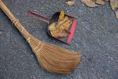 Escoba de Brown y cucharada del plástico con las hojas secas en el asfalto imágenes de archivo libres de regalías