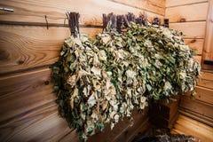 Escobas de abedul en una pared de madera en baño del russain Imágenes de archivo libres de regalías