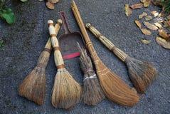Escobas de Brown y una cucharada roja en el asfalto gris con las hojas caidas secas imagen de archivo