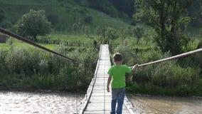 Escoja al niño valiente con el paso trasero sobre el puente de madera frágil, río de la montaña, valor metrajes
