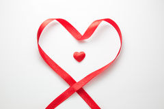 Escoja el corazón rojo rodeado por la cinta roja en forma de corazón Imagen de archivo libre de regalías