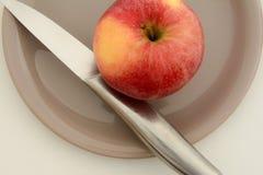 Escoja la manzana roja con un cuchillo en una placa Foto de archivo libre de regalías