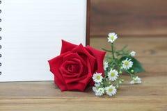 Escoja rosas rojas y un libro blanco en fondo de madera Imagen de archivo