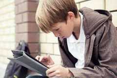 Escola adolescente com assento eletrônico da tabuleta Fotos de Stock