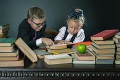 A escola caçoa a leitura de um livro na biblioteca Imagem de Stock