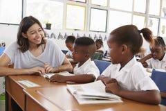 A escola de ajuda do professor voluntário caçoa na sala de aula, fim acima fotografia de stock