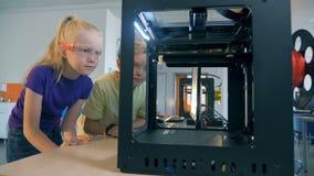 A escola entusiasmado caçoa usando a impressora tridimensional para criar o robô impresso 3D video estoque