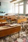 A escola jogada e destruída em Pripyat após o acidente de Chernobyl em Ucrânia em 1986 Mesas da escola e livros de texto dispersa fotografia de stock royalty free