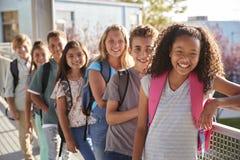A escola primária caçoa com as trouxas que sorriem na câmera fotos de stock