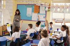 A escola primária caçoa levantar as mãos na classe para responder ao professor fotografia de stock
