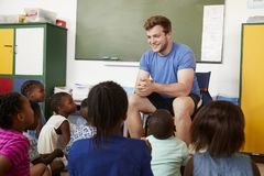 A escola primária caçoa o assento no assoalho que escuta um professor fotografia de stock royalty free