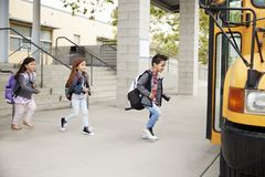 A escola primária caçoa sair da escola para pegar o ônibus escolar imagens de stock
