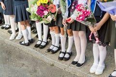 Escola primária das meninas com os ramalhetes das flores em suas mãos Sapatas em suas meia-calça do pé e as brancas, peúgas e mei Fotografia de Stock