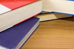 Escola, uma pilha de livros vermelhos e azuis em uma tabela de madeira Fotos de Stock