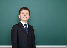 Escolar acertado feliz en retrato negro del traje en el fondo verde de la pizarra, concepto de la educación Imagenes de archivo