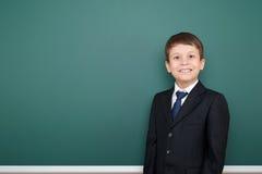 Escolar acertado feliz en retrato negro del traje en el fondo verde de la pizarra, concepto de la educación Foto de archivo