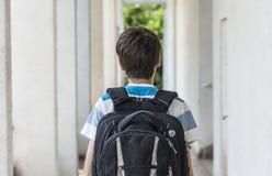 Escolar adolescente con una mochila en el suyo parte posterior que camina a la escuela Fotos de archivo