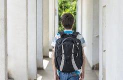Escolar adolescente con una mochila en el suyo parte posterior que camina a la escuela Imagen de archivo libre de regalías