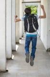 Escolar adolescente con una mochila en el suyo parte posterior que camina a la escuela Imágenes de archivo libres de regalías