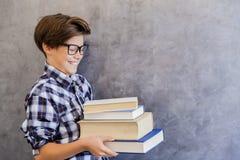 Escolar adolescente lindo que sostiene los libros Foto de archivo libre de regalías