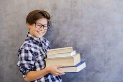 Escolar adolescente lindo que sostiene los libros Fotografía de archivo