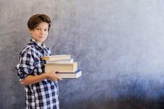 Escolar adolescente lindo que sostiene los libros Fotos de archivo libres de regalías