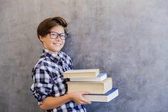 Escolar adolescente lindo que sostiene los libros Foto de archivo