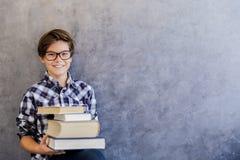 Escolar adolescente lindo que sostiene los libros Fotos de archivo