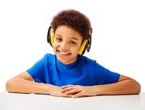 Escolar afroamericano alegre con las auriculares Imagen de archivo libre de regalías
