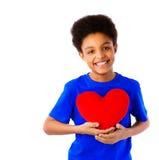Escolar afroamericano que lleva a cabo el corazón de las tarjetas del día de San Valentín Fotografía de archivo
