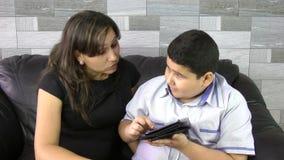 Escolar elemental que estudia en la tableta con la madre en casa almacen de video