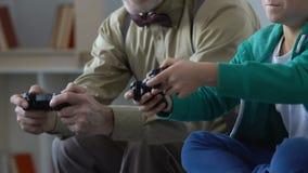 Escolar emocionado que compite en el videojuego con el abuelo, proximidad de la familia almacen de metraje de vídeo