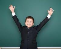 Escolar en brazos abiertos del traje negro en el fondo verde de la pizarra, concepto de la educación Fotos de archivo libres de regalías