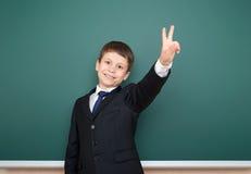 Escolar en gesto negro del finger de la demostración dos del traje en el fondo verde de la pizarra, concepto de la educación Imagenes de archivo