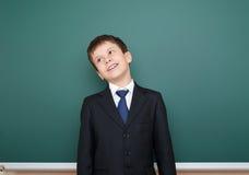 escolar en retrato negro del traje en el fondo verde de la pizarra, concepto de la educación Fotos de archivo libres de regalías