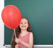 Escolar en traje negro en el fondo verde de la pizarra, concepto de la educación Imagen de archivo libre de regalías