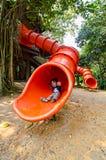 Escolar feliz del niño pre que desliza abajo la diapositiva roja Foto de archivo libre de regalías