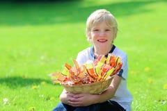 Escolar feliz que sostiene la cesta llena de huevos de Pascua Imagen de archivo libre de regalías