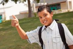 Escolar hispánico joven feliz con los pulgares para arriba Fotos de archivo