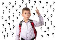 Escolar inteligente con la idea para contestar a la pregunta difícil, rodeada con los signos de interrogación Fotos de archivo libres de regalías