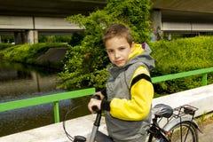 Escolar joven con la bicicleta en el puente Imagenes de archivo