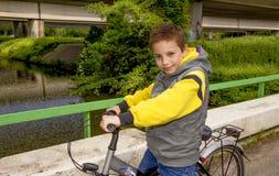 Escolar joven con la bicicleta en el puente Foto de archivo