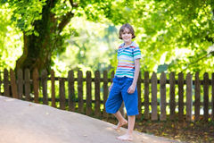 Escolar lindo en patio en día soleado caliente Foto de archivo