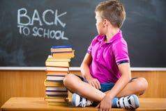 Escolar lindo que se sienta con los libros en sala de clase Imagen de archivo